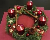 Schöner Adventskranz in grünen, roten und goldenen Farben.