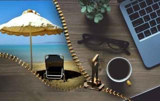 Schreibtisch mit Notebook, Brille, Kaffee und einer Liege am Meer hinter einem Reißverschluss