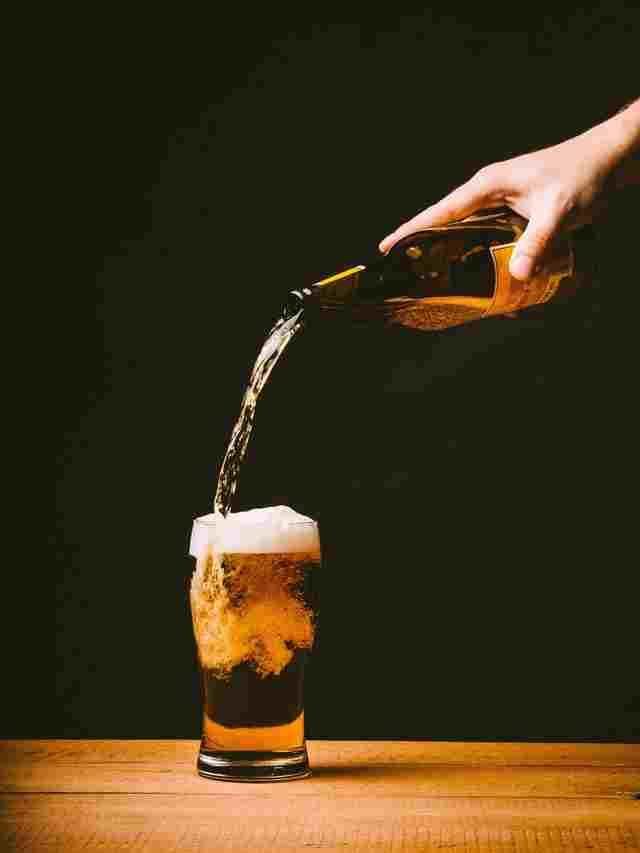 Einschenken eines Bieres aus der Flasche vor schwarzem Hintergrund