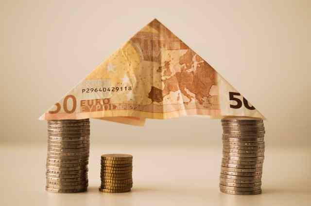Geldmünzen und ein Schein zu einem Haus gestapelt