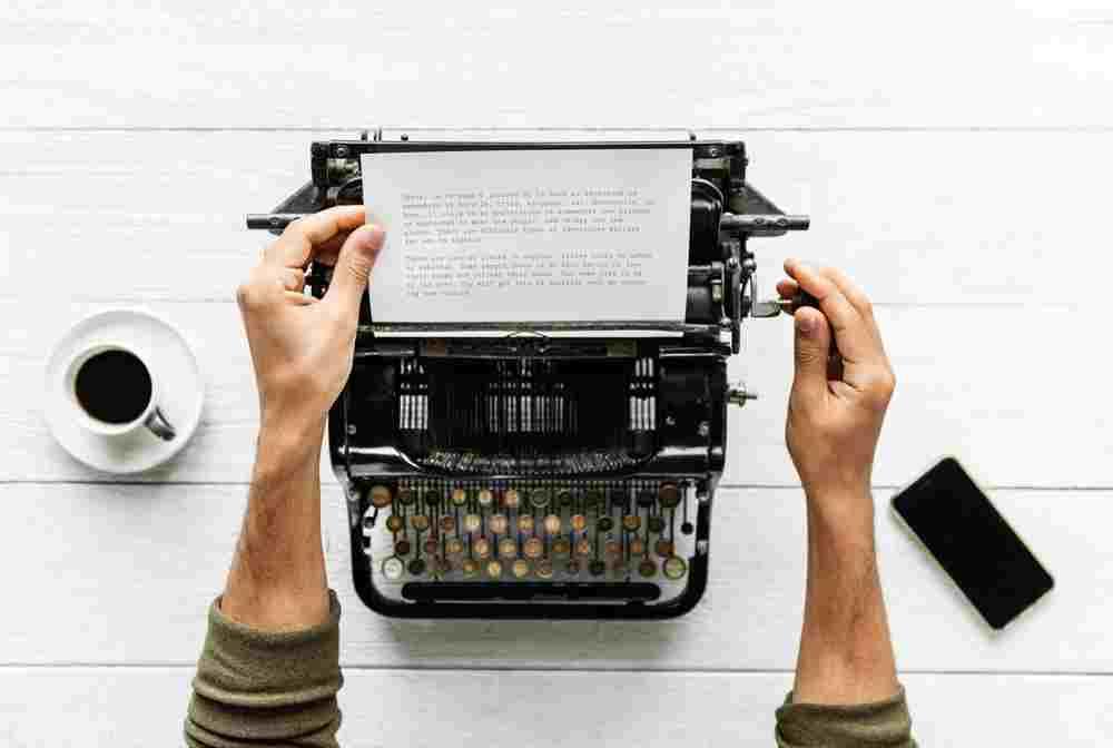 Alte Schreibmaschine von oben mit beschriftetem Papier